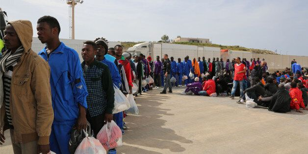Migrants board on a cruise ship as they leave the Island of Lampedusa, Southern Italy, to be transferred...