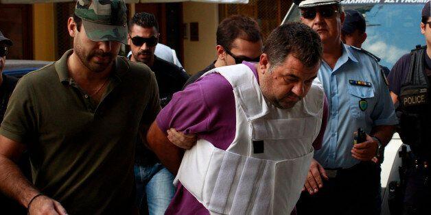 PIRAEUS, GREECE - SEPTEMBER 21: Policemen escort George Roupakias, who is accused in the fatal stabbing...