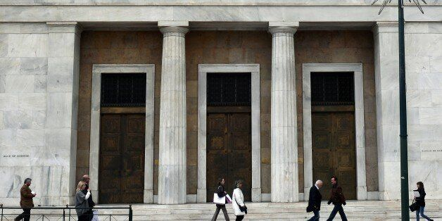 People walk past Bank of Greece headquarters in Athens on March 6, 2015. Greek Prime Minister Alexis...