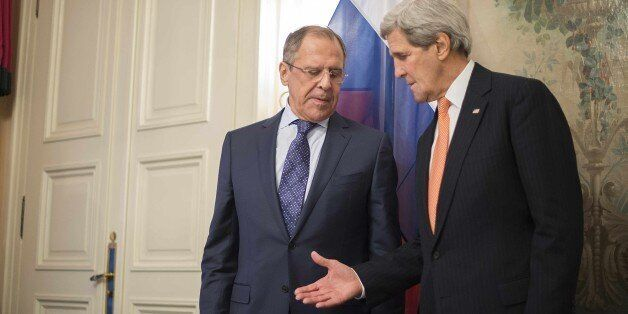 US Secretary of State John Kerry (R) reaches out to shake hands with Russian Foreign Minister Sergey...