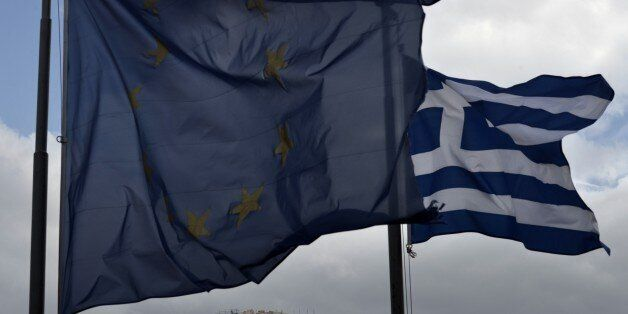 A Greek and an EU flag wave in front of the ancient temple of Parthenon atop the Acropolis hill in Athens...