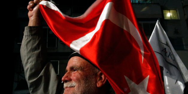 A supporter of the leadership candidate Mustafa Akinci waves a Turkish flag during a rally in the old...