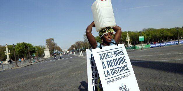 Gambian woman Siabatou Sanneh displays a sandwich board which translates as 'Help us to reduce the distance'...