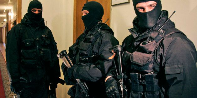 Ukrainian national security service armed agents wearing masks raid the headquarters of the country's...