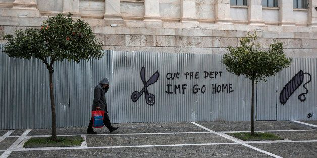 A pedestrians passes graffiti reading 'Cut The Debt, IMF Go Home' on corrugated fencing outside the Academy...