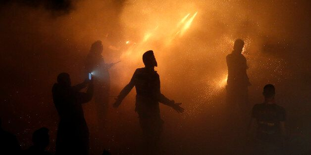 Men ignite rockets during Greek Orthodox Easter celebrations on the eastern Aegean island of Chios, Greece,...