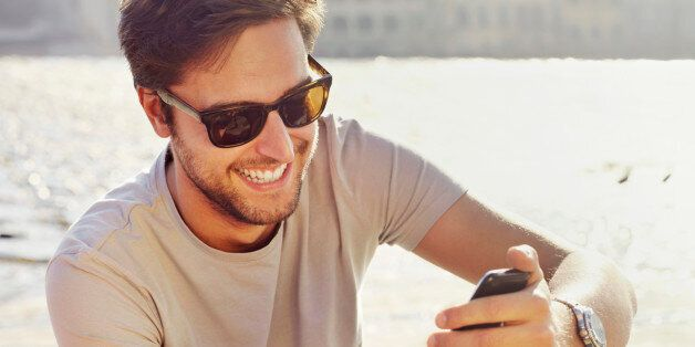 one young man, casual, outdoor, sunlight, day, clear sky, sitting, leisure, technology, mobile phone,...