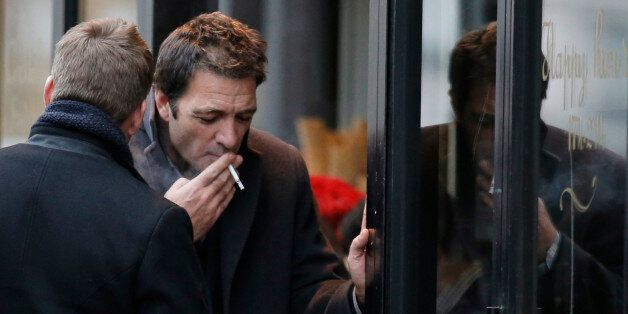 British businessman Ian Griffin, right, and an unidentified person smokes a cigarette during a break...