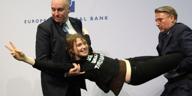 A woman is stopped by security after she interrupted a press conference by Mario Draghi, President of...