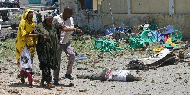 A wounded woman is helped at the scene of a car bomb outside the Education Ministry in Mogadishu on April...