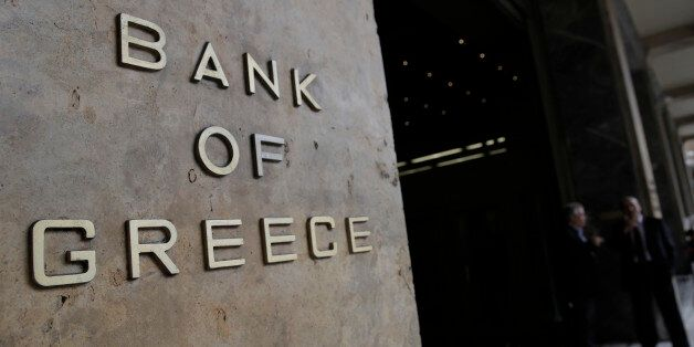 People walk past the Bank of Greece headquarters, in central Athens, on Friday, March 6, 2015 . European...