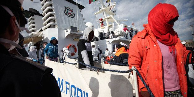 Migrants disembark from an Italian Coast Guard vessel after being rescued in Porto Empedocle, Sicily,...
