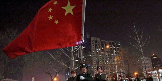 In this Tuesday, March 24, 2015 photo, a Chinese man holding a national flag leads his members of friend...