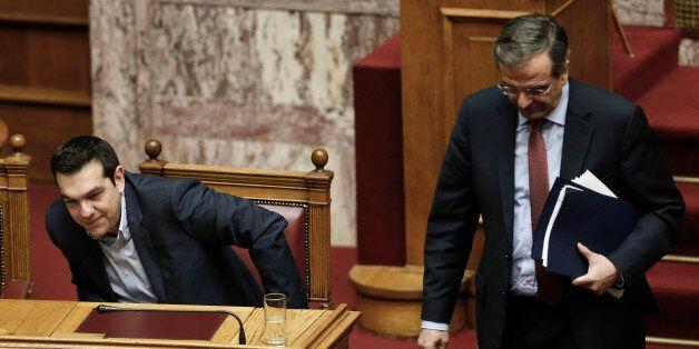 Greece's former Prime Minister Antonis Samaras walks past Greece's Prime Minister Alexis Tsipras, left,...