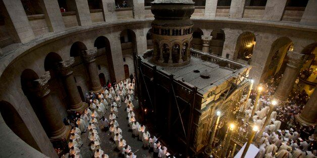 Christian clergymen hold candles during a procession at the Church of the Holy Sepulchre, traditionally...