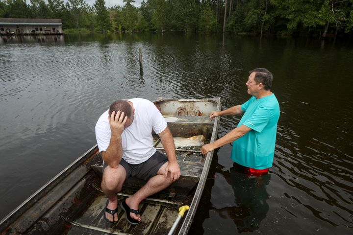 Stephen Gilbert, left, and his father-in-law sit in front of their flooded property on Friday, Sept. 20, 2019, in the Maurice