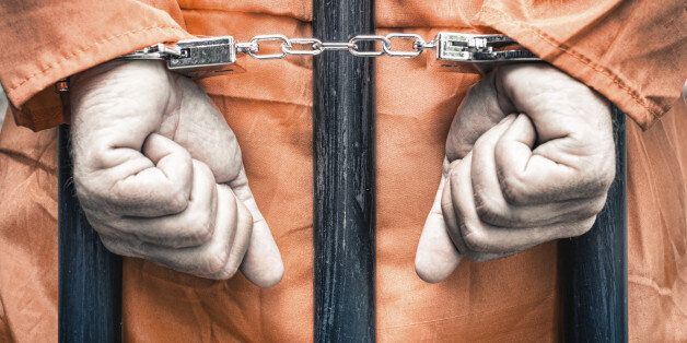 Handcuffed hands of a prisoner behind the bars of a prison with orange clothes - Crispy desaturated dramatic...