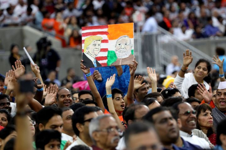 "A boy holds a placard depicting President Donald Trump and India's Prime Minister Narendra Modi during the ""Howdy Modi"" event"