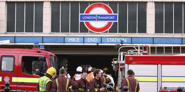 Firefighters stand outside Mile End tube station, London, after a tube derailed on the westbound Central...