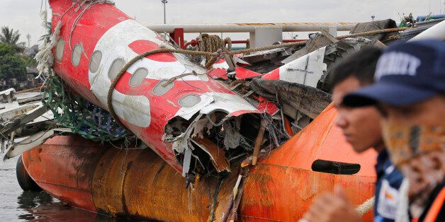 Security guards stand near the newly-recovered remains of the fuselage of the ill-fated AirAsia Flight...