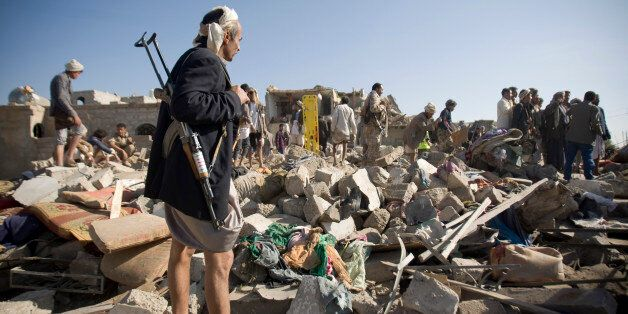 A Houthi Shiite fighter stand guard as people search for survivors under the rubble of houses destroyed...