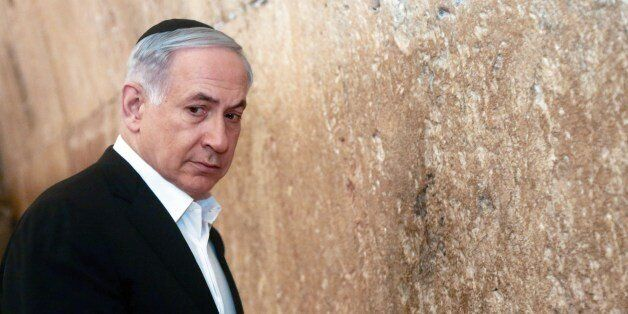 Israeli Prime Minister Benjamin Netanyahu looks on before praying at the Western Wall, the holiest site...