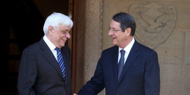 Cyprus' President Nicos Anastasiades, left, and President of Greece, Prokopis Pavlopoulos, prepare to...