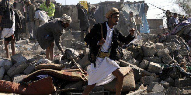 SANAA, YEMEN - MARCH 26: Yemeni men search for survivors in rubble of buildings after airstrikes of a...