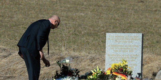 A man lays flowers at a memorial for the victims of the Germanwings plane crash in Le Vernet on March...