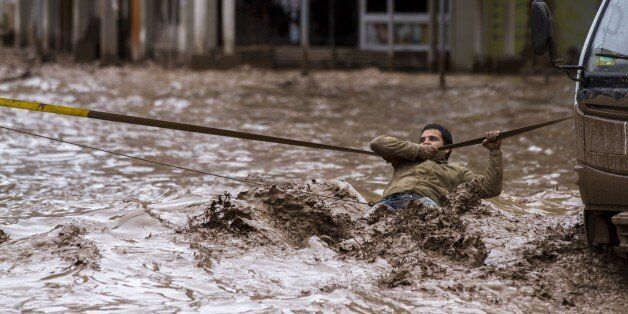 A man clings to a security line to cross a street flooded by the overflowing of the Copiapo River due...