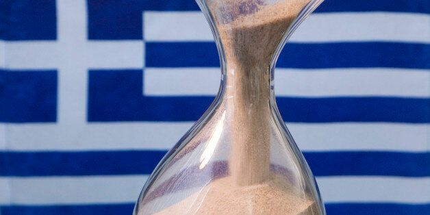 GERMANY, BONN - MARCH 17: Sand glass and a Greek flag.Our picture shows a running sand glass and the...