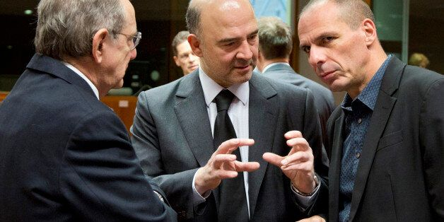 Greek Finance Minister Yanis Varoufakis, right, speaks with European Commissioner for the Economy Pierre...
