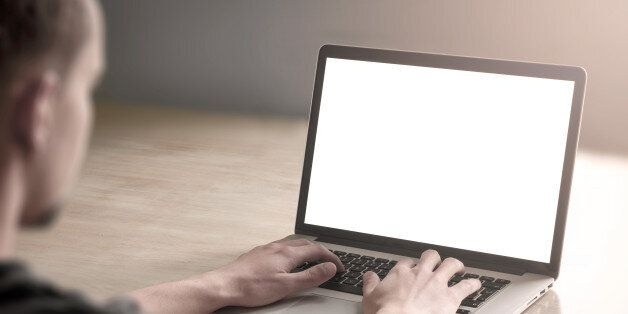 Man working on his laptop computer with blank