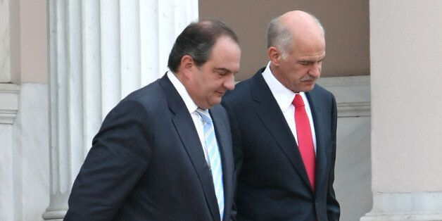 Newly elected Greek Prime Minister George Papandreou, right, escorts outgoing Prime Minister Costas Karamanlis...