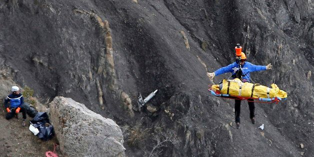 FILE - In this Thursday March 26, 2015 file photo a rescue worker is lifted into an helicopter at the...