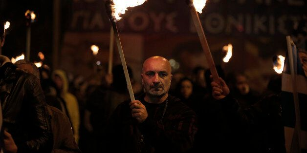 Supporters of Greece's extreme right party Golden Dawn, hold torches during a rally to commemorate a...