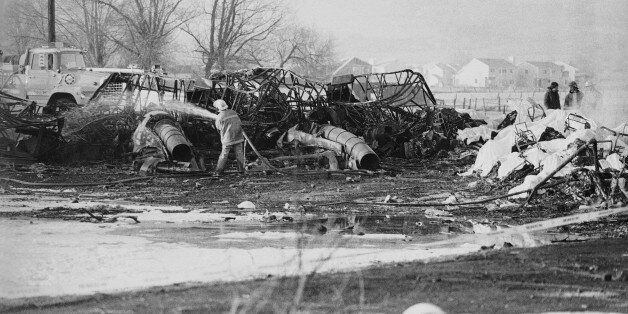 FILE - In this Jan. 21, 1985, file photo, a fireman hoses down an aircraft wreckage, Galaxy Airlines...