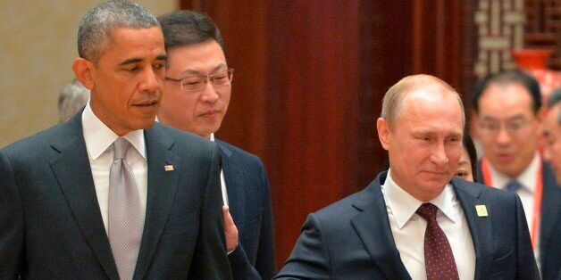 Russian President Vladimir Putin, right, passes by US President Barack Obama at the Asia-Pacific Economic...