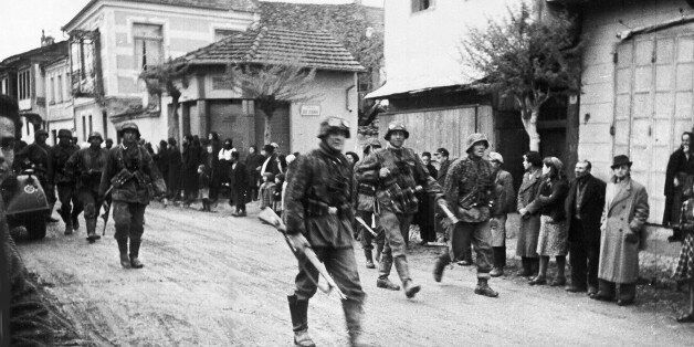 A squad of German soldiers pass through a Greek village, during the occupation of Greece, in May 1941....