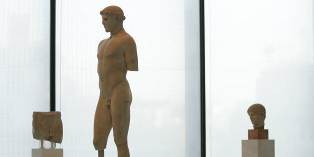 A 2,600-year-old marble statue of a youth is displayed in the new Acropolis Museum in Athens, Greece,...
