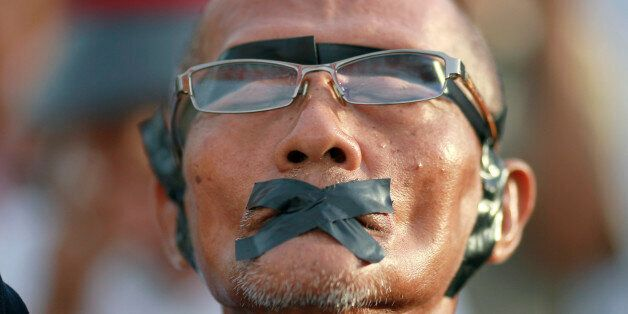 A protester displays how his rights were violated during an anti-coup demonstration at the Victory Monument...