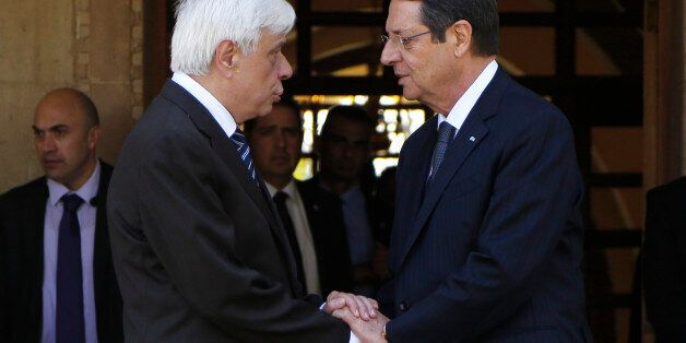 Cyprus' President Nicos Anastasiades, right, and President of Greece, Prokopis Pavlopoulos, talk as they...