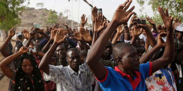 People displaced following attacks by Islamist militants raise their arms as they pass through security...