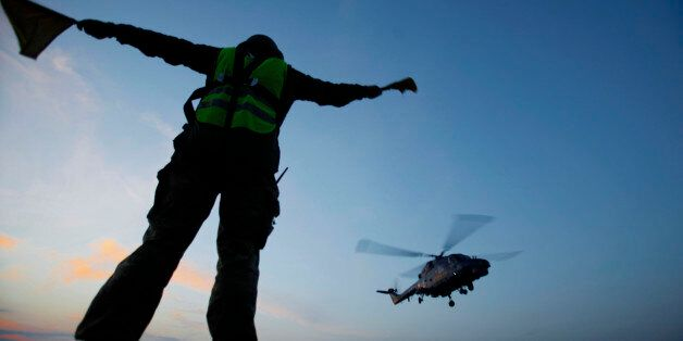 A member of the Danish military personnel gives the signal to a Danish air force helicopter to leave...