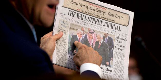 Secretary of State John Kerry points to a photograph on the front page of the Wall Street Journal as...