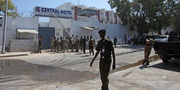 Somali security forces gather outside the scene of a twin bombing attack on a hotel in the capital Mogadishu,...