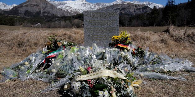 A stele and flowers laid in memory of the victims are placed in the area where the Germanwings jetliner...
