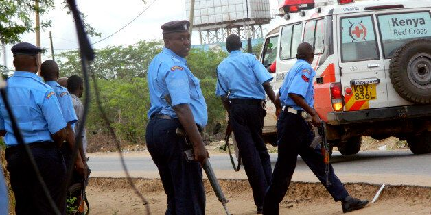 Kenyan police officers take positions outside the Garissa University College as an ambulance carrying...