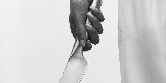 Man's hand holding large hand gun, close
