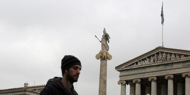A man walks past the Athens Academy with the 19th century statue of the ancient goddess Athena, on Friday,...